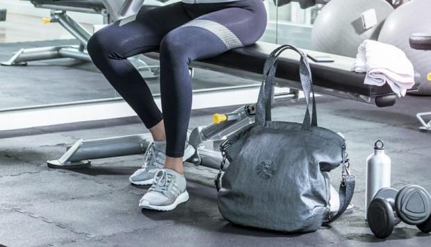 mujer con el bolso de entrenamiento en gimnasio